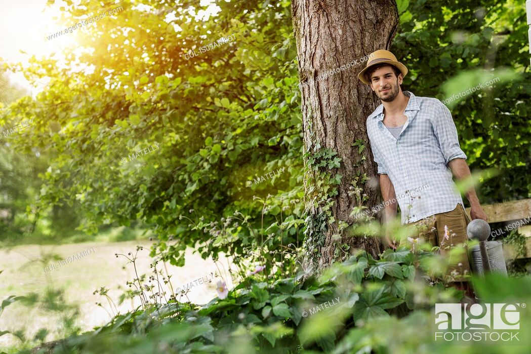 Stock Photo: Young man leaning against tree with watering can.