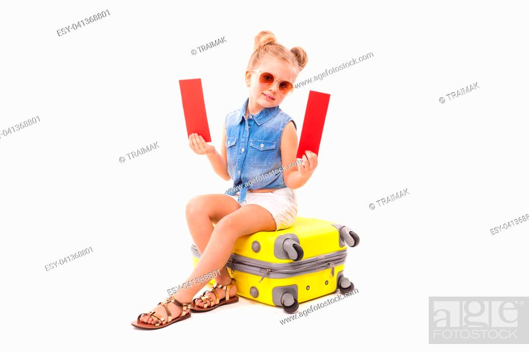 Stock Photo: Isolated on white, pretty little caucasian blonde girl in blue jeans shirt, white shorts, sunglasses and sandals sit on the yellow suitcase.