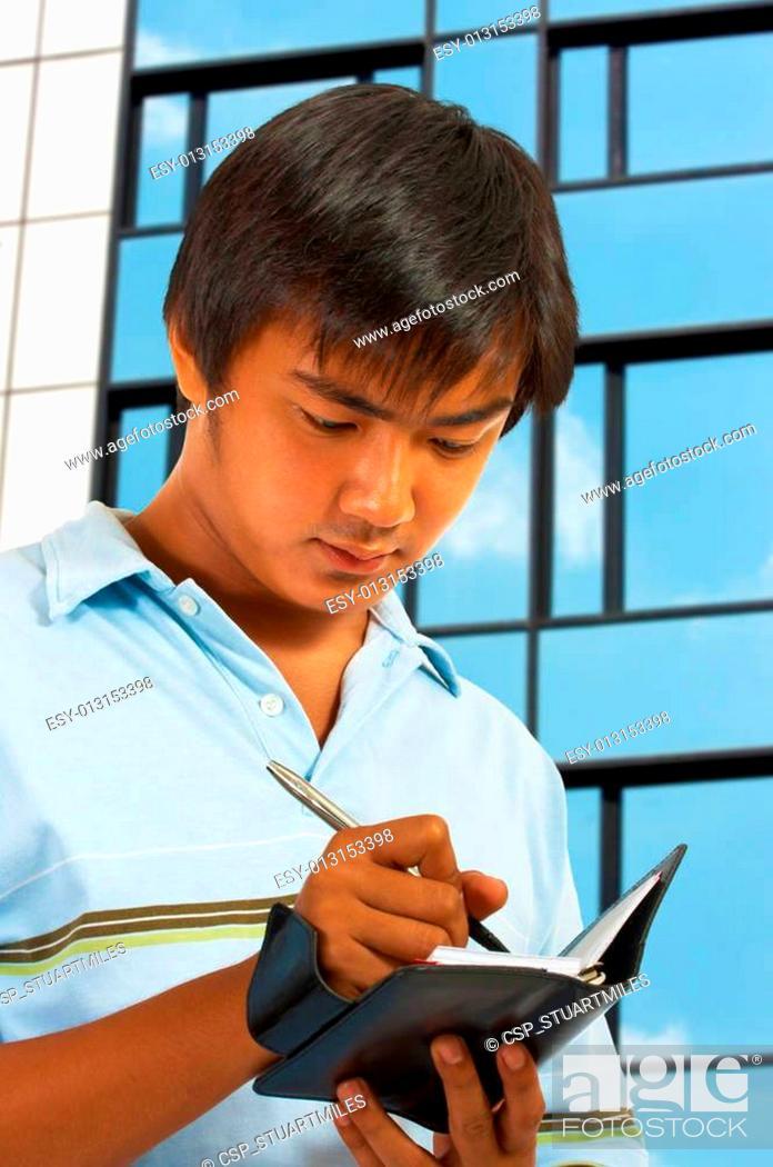 Stock Photo: Man Writing In His Organizer.