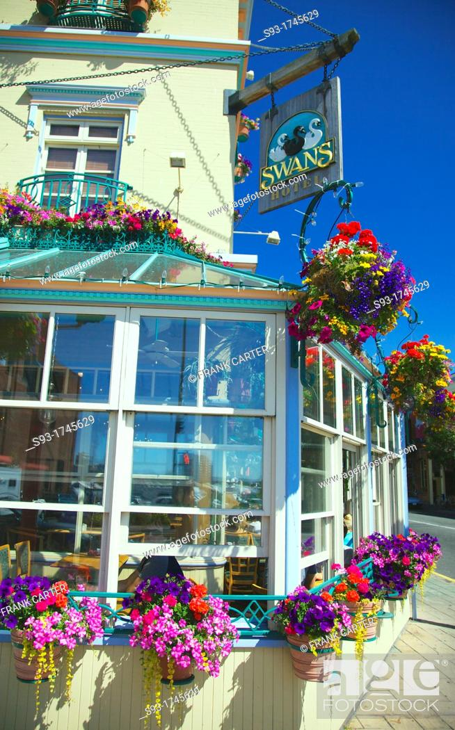 Stock Photo: A view of the Swan Hotel in downtown Victoria showing hanging flower pots all around it.