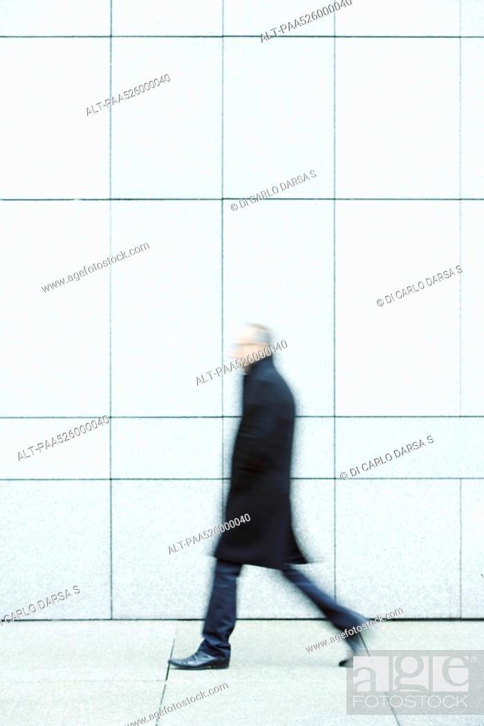 Stock Photo: Businessman walking alone hands in pockets down sidewalk.