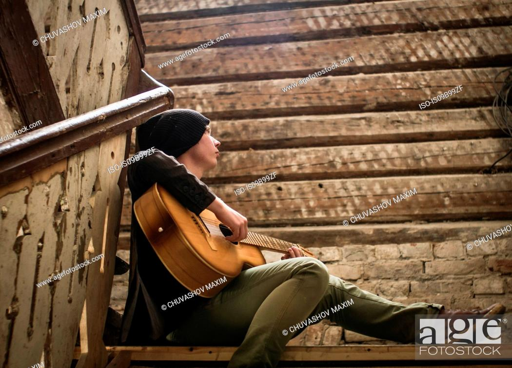 Stock Photo: Young man sitting on stairs, playing guitar.