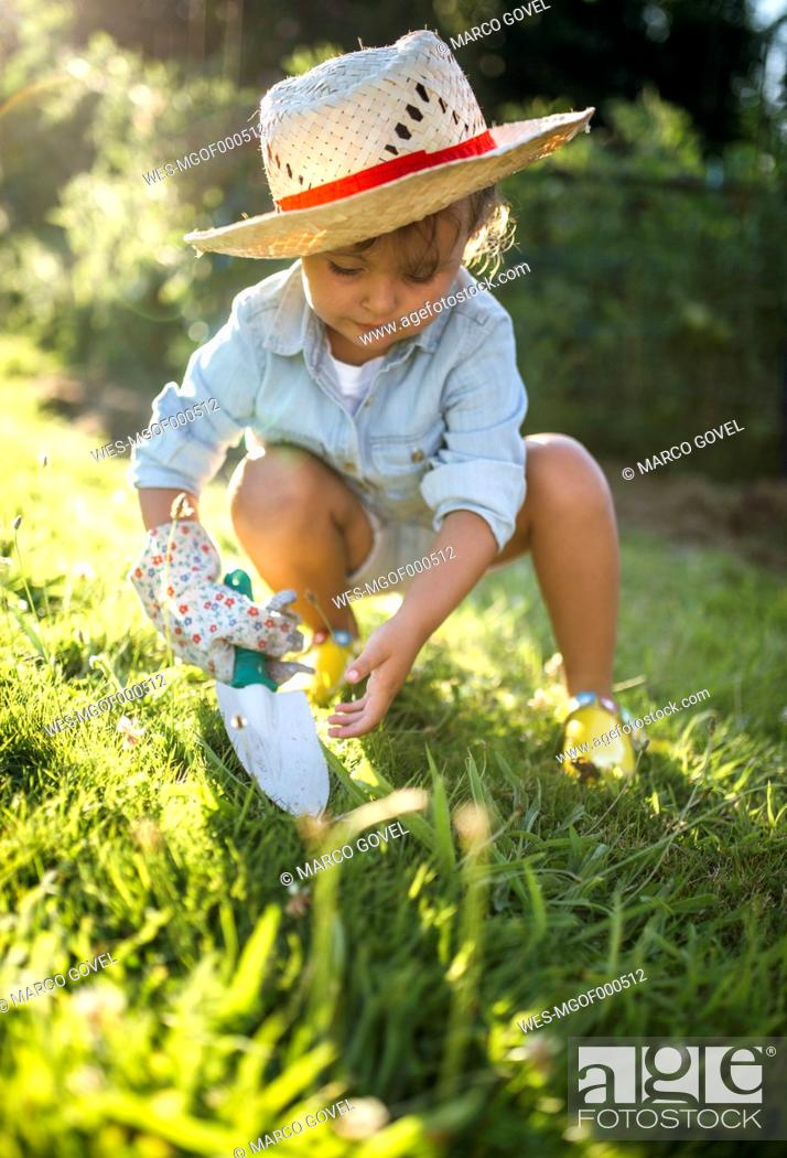 Stock Photo: Little girl crouching with gardening glove and hand trowel on a meadow.