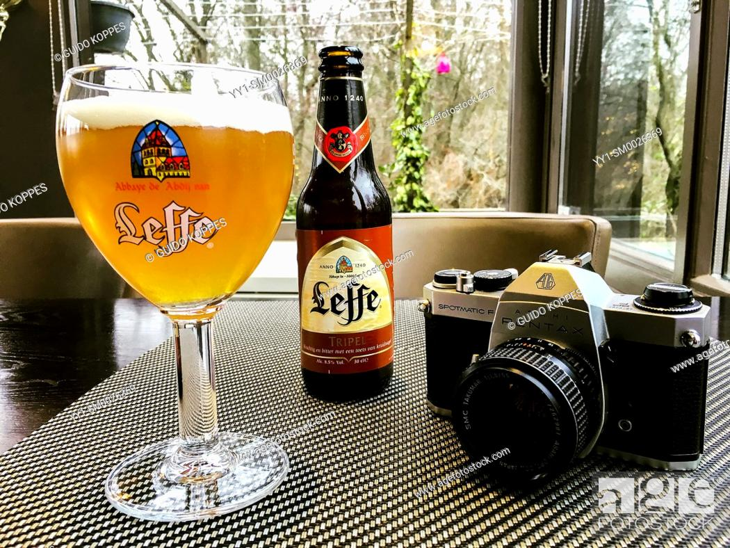 Imagen: Rotterdam, Netherlands. Analog mirror reflex camera on a cafe's table, neighbored by a glass of beer and a beerbottle during a walkbreak of a photographer.