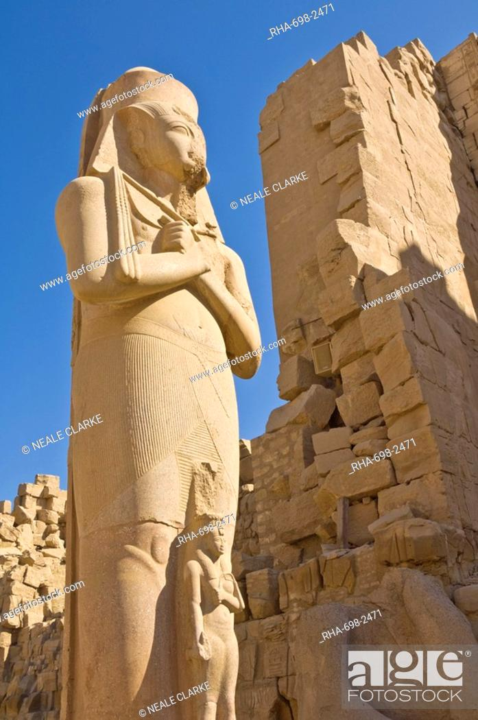 Stock Photo: Giant statue of the great pharaoh Rameses II with the small statue of his daughter Bent'anta between his legs in the forecourt behind the first Pylon of the.