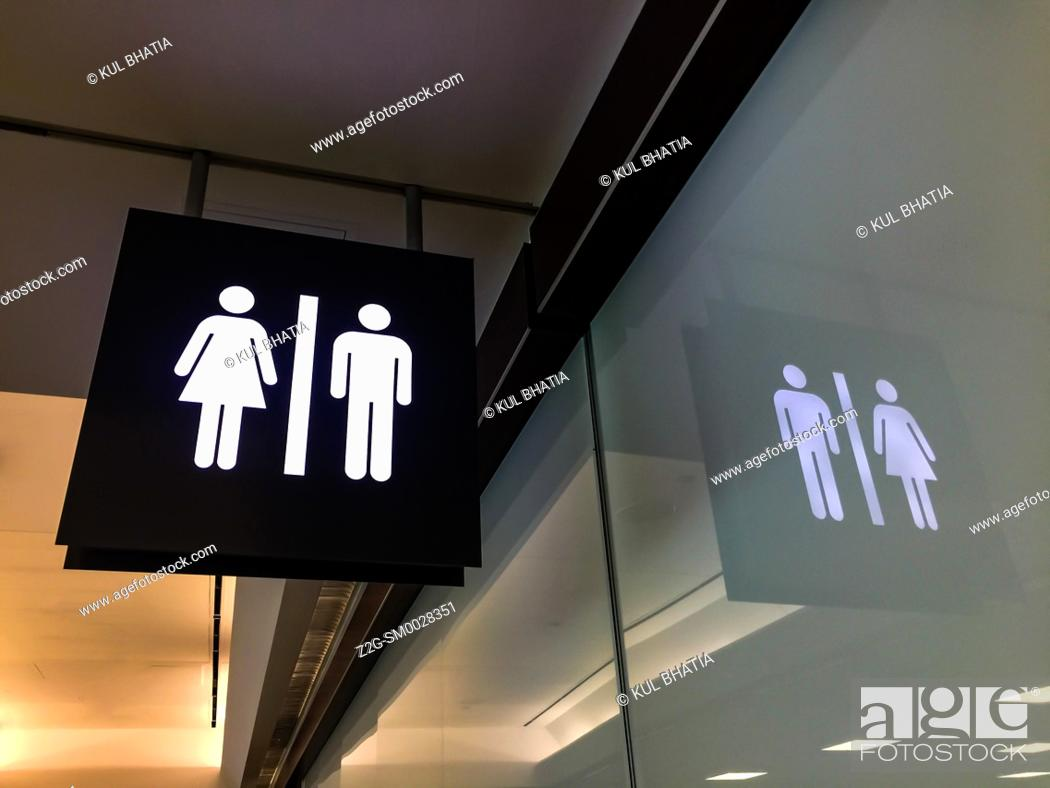 Stock Photo: Pictograph of washroom sign, installed high near the ceiling, for males and females, in a modern airport, Canada.