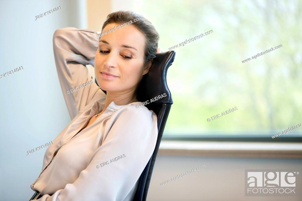 Stock Photo: Businesswoman day dreaming in an office.