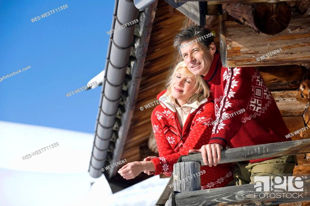 Stock Photo: Italy, South Tyrol, Seiseralm, Couple standing on deck of log cabin.