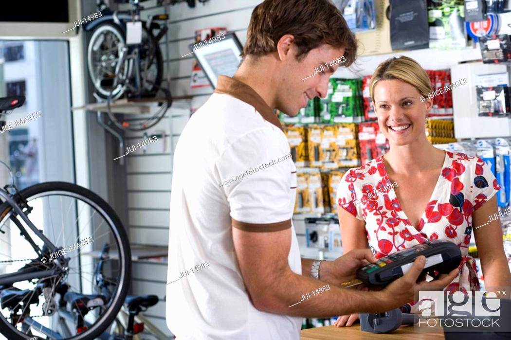 Stock Photo: Storekeeper serving customer in shop, smiling.