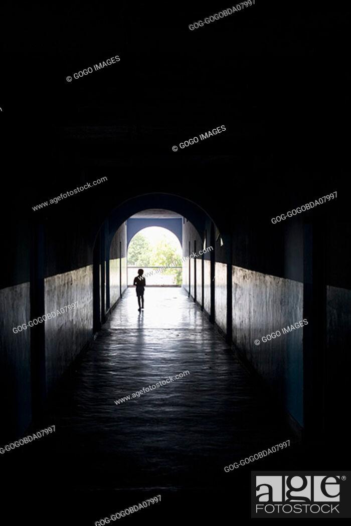 Stock Photo: Child walking through a dark hallway.