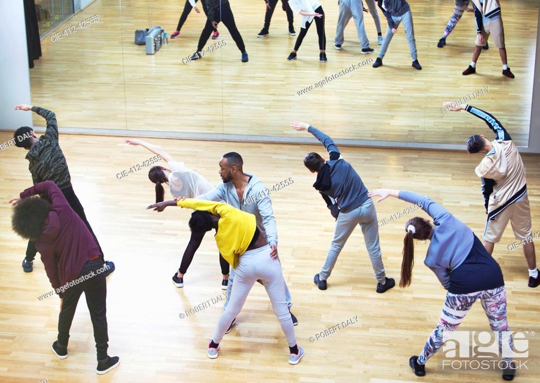 Imagen: Instructor guiding students in dance class studio.