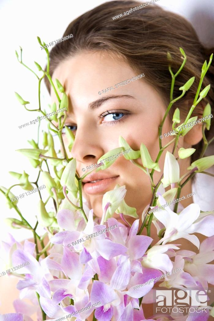 Stock Photo: woman holding bunch of orchid.