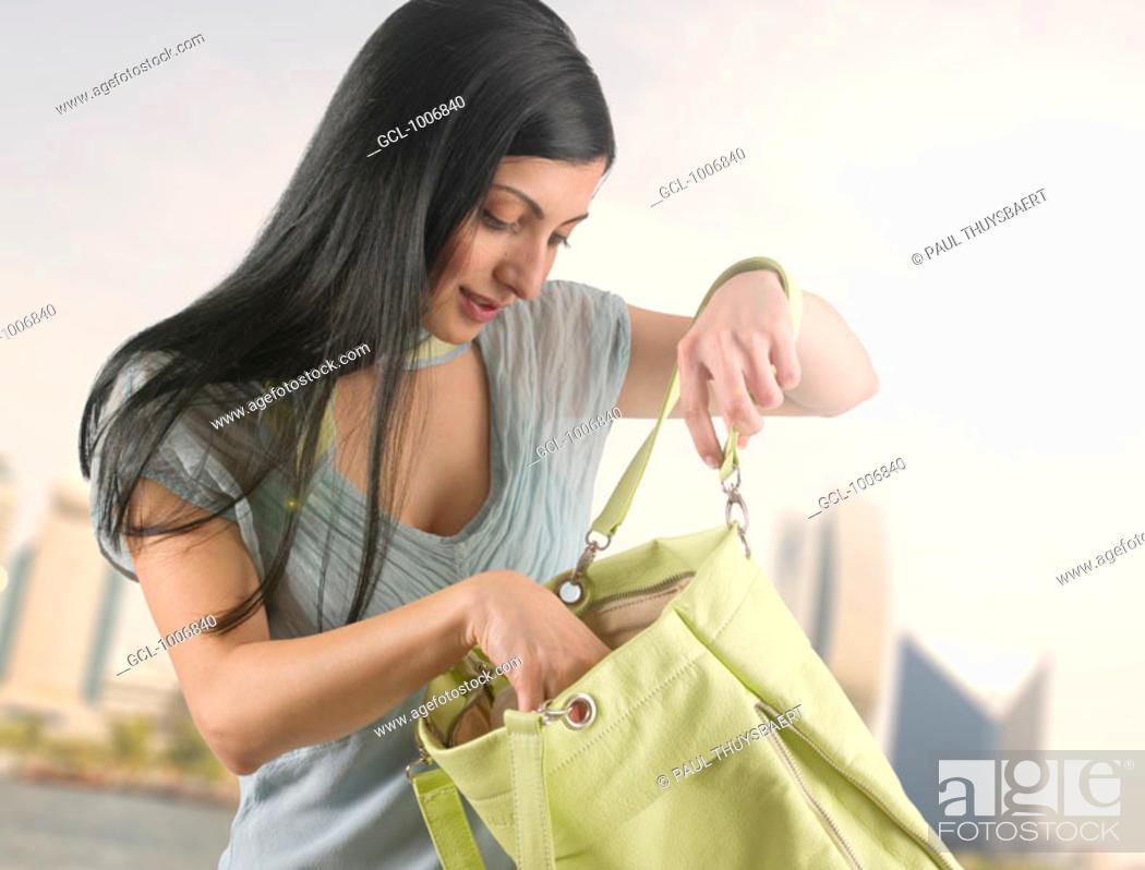 Stock Photo: Arab female tourist checking her handbag at the creek in Dubai.