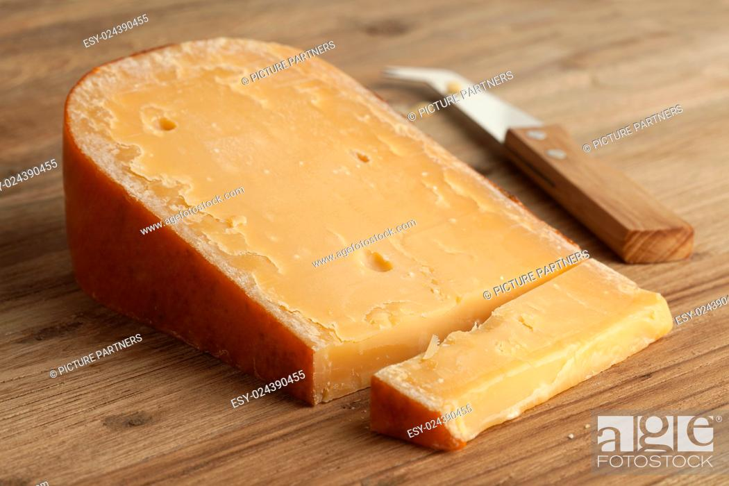 Photo de stock: Piece of three year old Gouda cheese on a cheeseboard.
