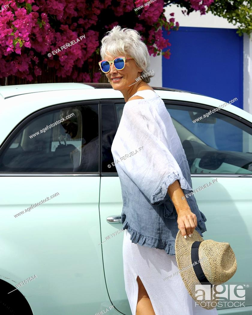 Stock Photo: Mature woman in a white suit enjoying an afternoon on the Islantilla beach, Huelva.