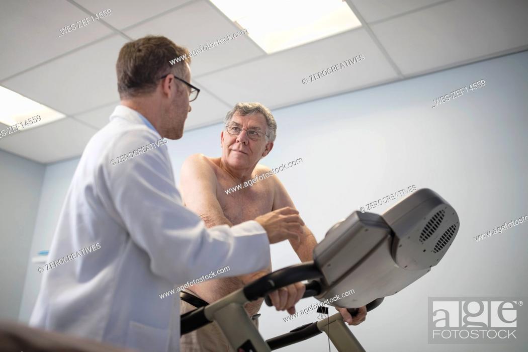 Stock Photo: Doctor talking to senior patient on treadmill.