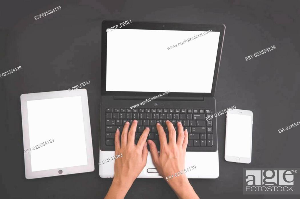 Stock Photo: Hands typing on laptop with tablet and mobile phone on the side. on black background, mock up.
