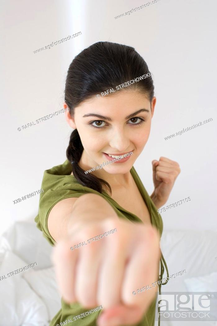 Stock Photo: young woman training tai-chi at home.