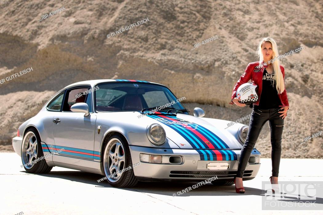 Stock Photo: Young woman with long blonde hair poses with Porsche 911 Carrera 4.