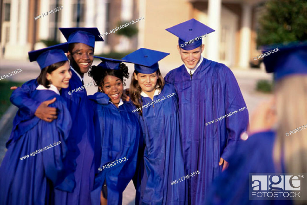 Stock Photo: Group of students standing together wearing their graduation outfits.