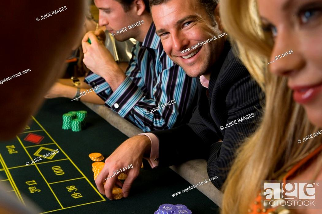 Stock Photo: Man gambling at roulette table, smiling, portrait.