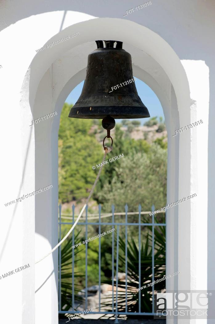 Stock Photo: An old-fashioned bell hanging in an archway.