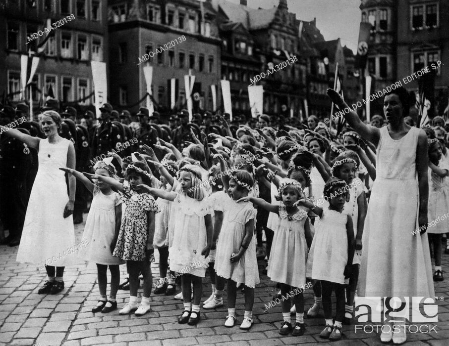 Stock Photo: Military parade of Nazi Assault Teams. A female student body making the Nazi salute during a military parade of the SA (Assault Squad) of the Nazi Party.