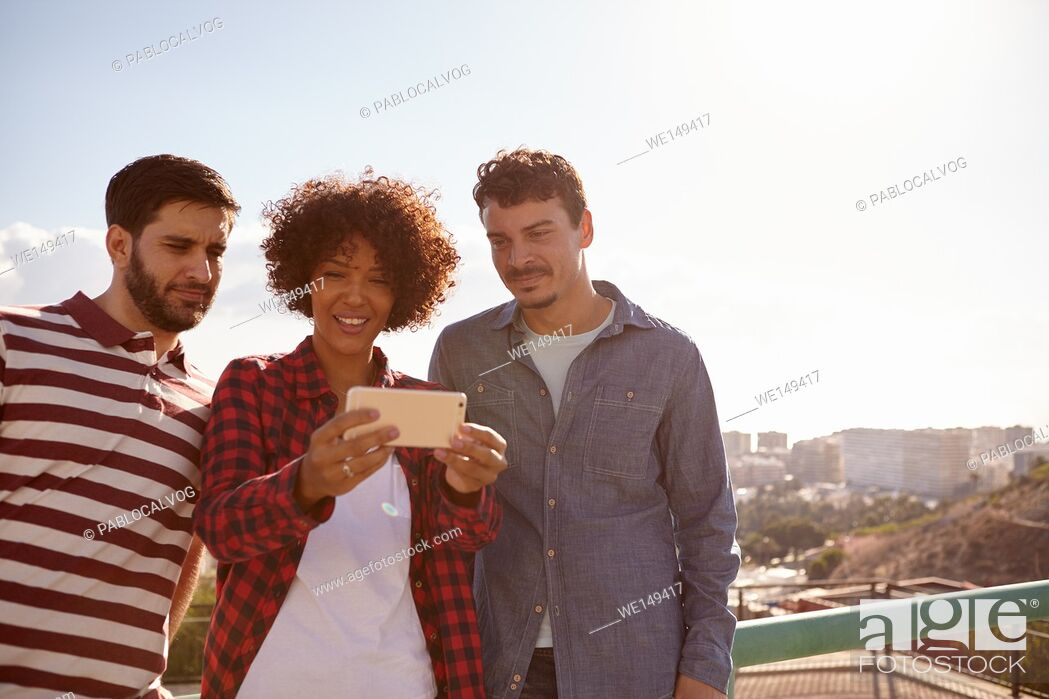 Stock Photo: Three young millennials looking at cellphone the girl with the toothy smile between the guys is holding up for them all to see.