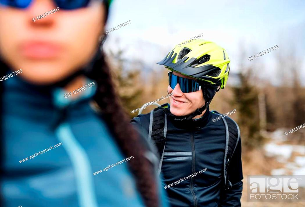 Imagen: Two mountain bikers standing on road outdoors in winter, resting.