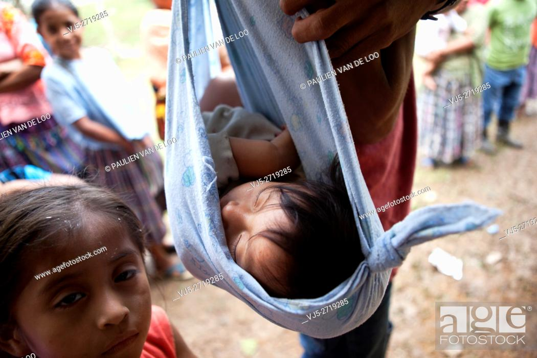 Stock Photo: Chahal, Guatemala, a child from a Maya tribe in the jungle is being carried in cloth by her father. Her sister is watching.