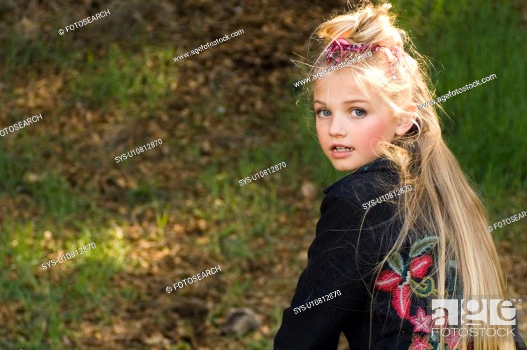 Stock Photo: Portrait of young blonde girl outside.