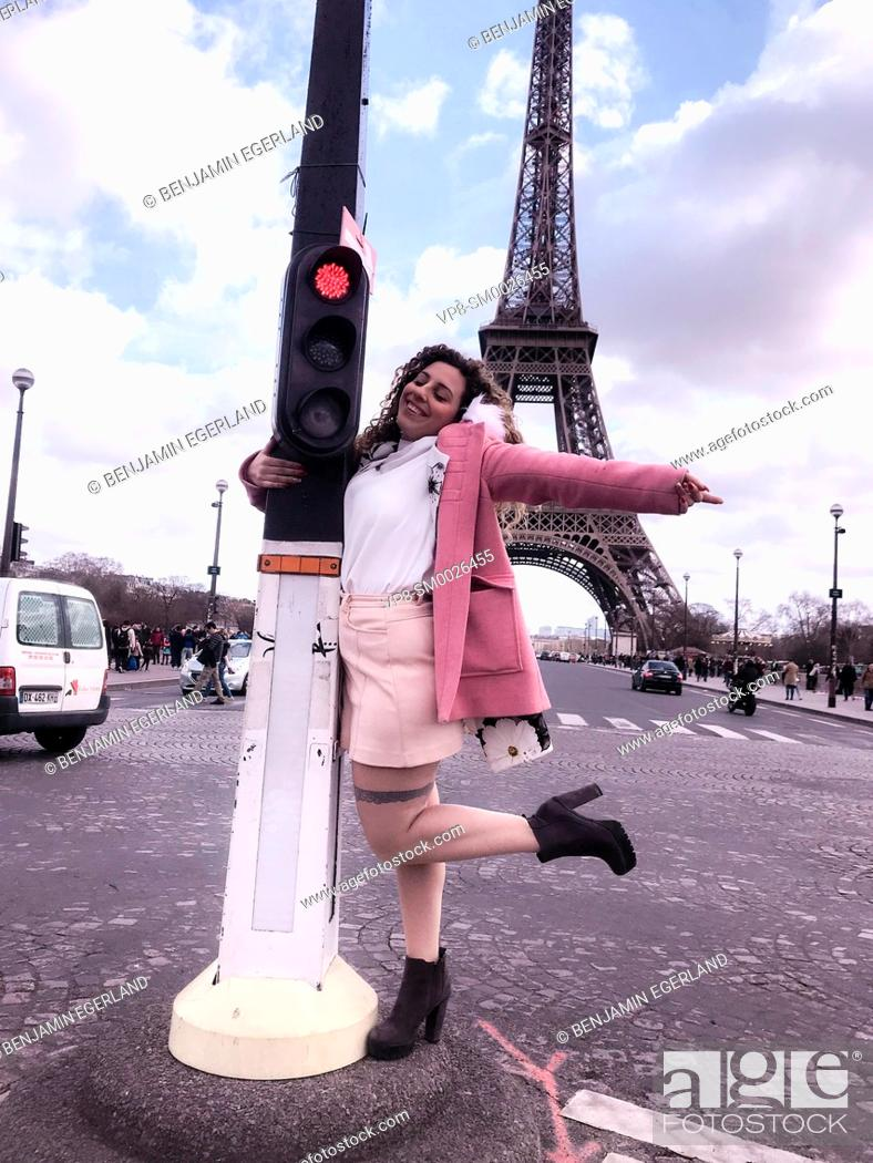 Imagen: young happy Millennial tourist woman dancing at street embracing red traffic lights, next to touristic sight Eiffel Tower, in Paris, France.