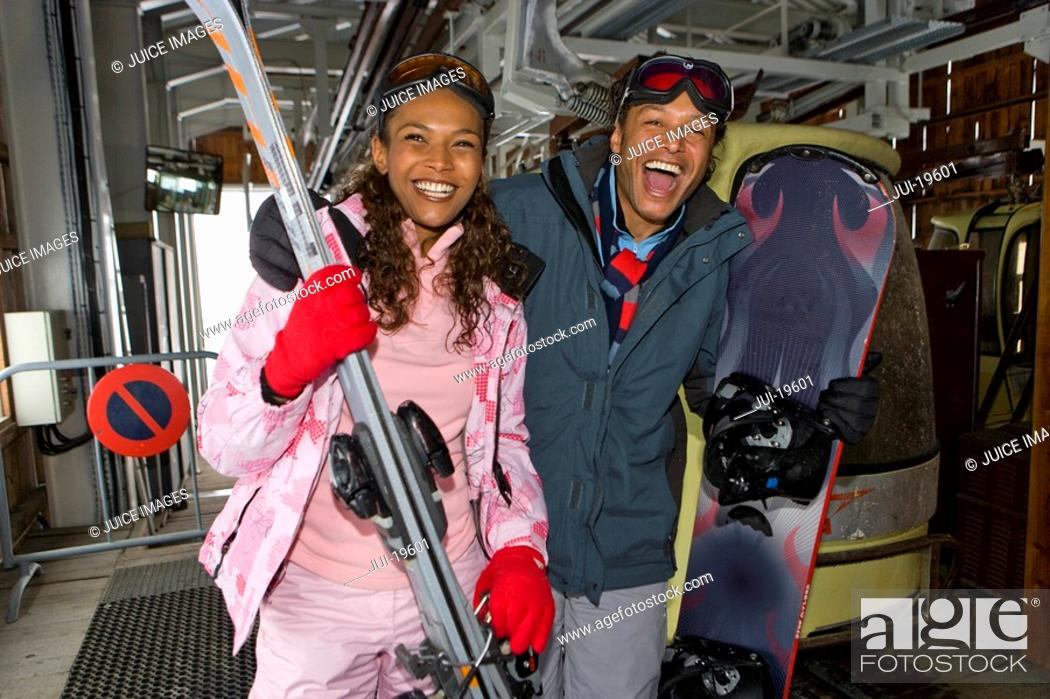 Stock Photo: Mixed race couple on ski lift with skis and snowboard.