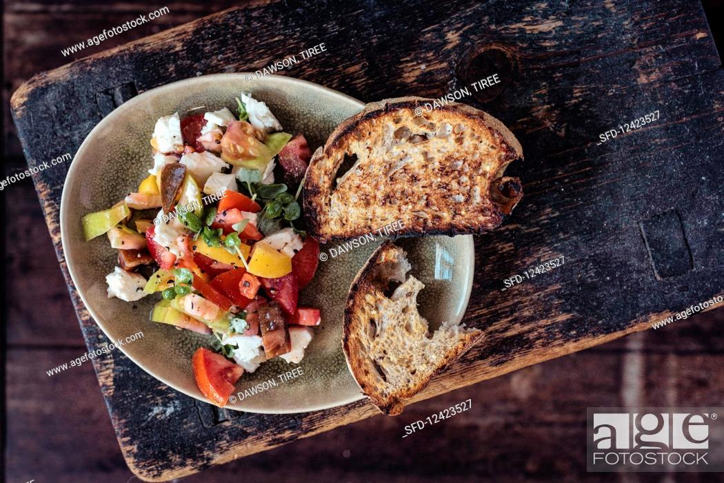 Photo de stock: Sourdough bruschetta with heritage heirloom tomatoes, mozarrella, baby basil, cracked black pepper and olive oil.