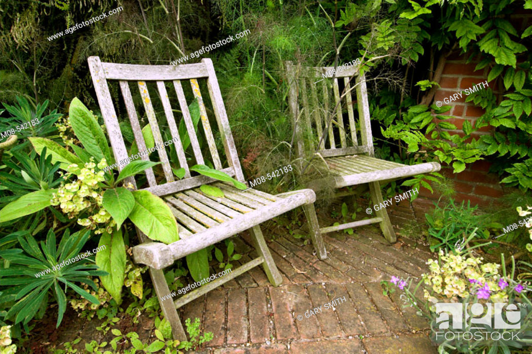 Stock Photo: Old rustic wooden garden chairs in a shady corner.