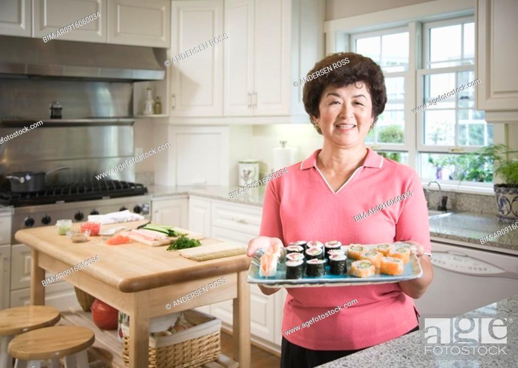 Stock Photo: Senior Asian woman holding tray of sushi.