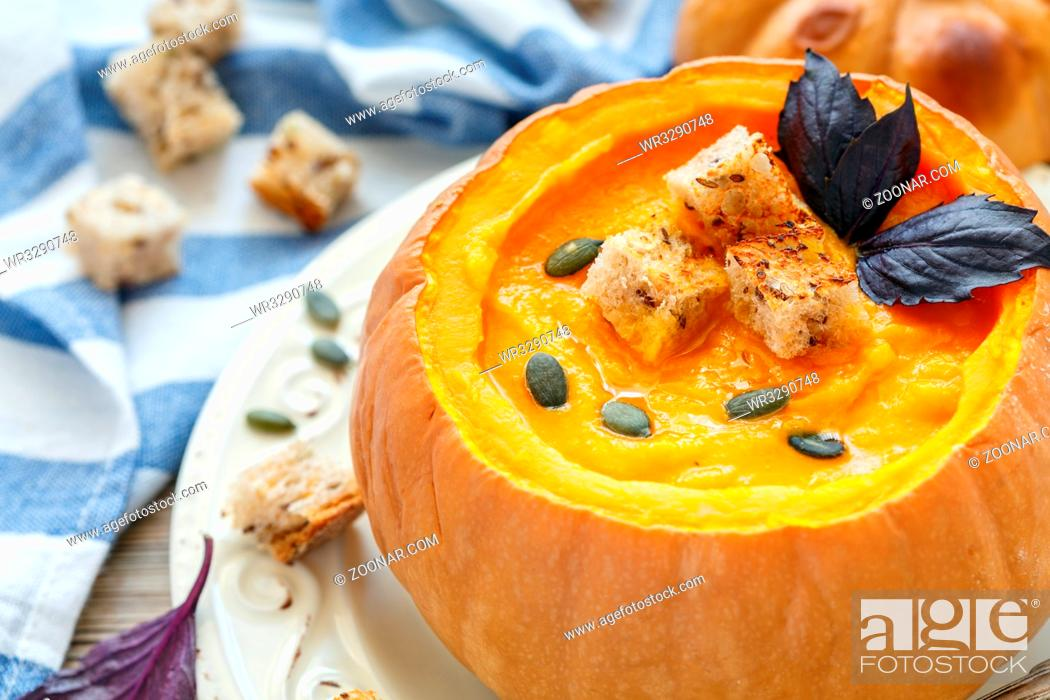Stock Photo: Pumpkin cream soup in a pumpkin on a white plate, selective focus.