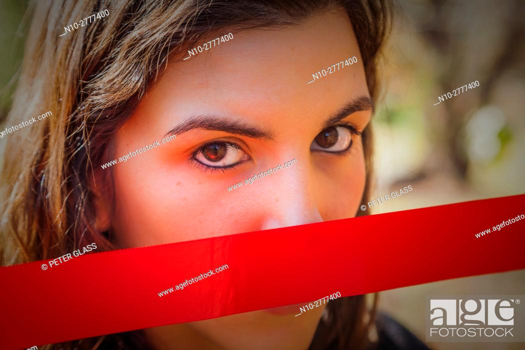 Stock Photo: Young woman, outdoors, holding a red ribbon over her mouth.