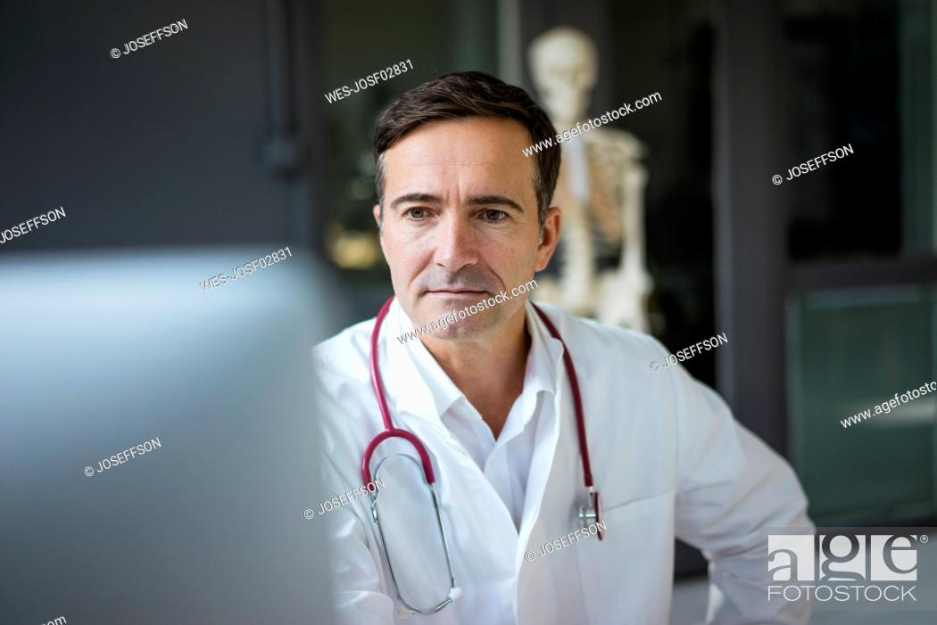Stock Photo: Doctor in medical practice looking at computer with skeleton in background.