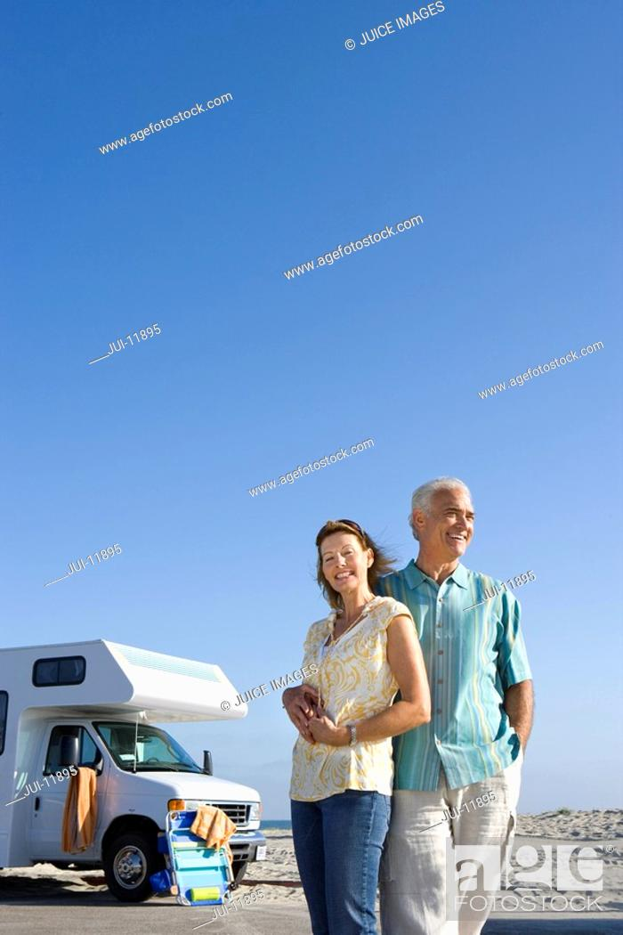 Stock Photo: Mature couple arm in arm by motor home on beach, smiling, low angle view.
