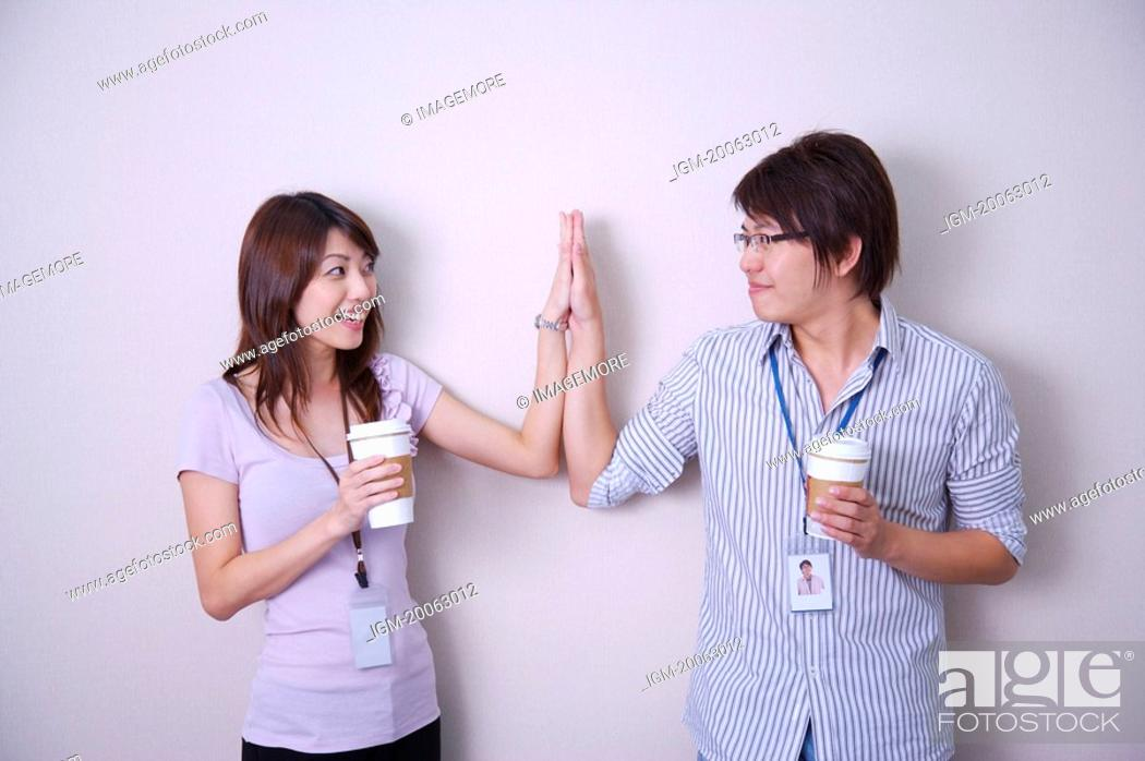 Stock Photo: Young man and woman holding coffee together and making high-five.