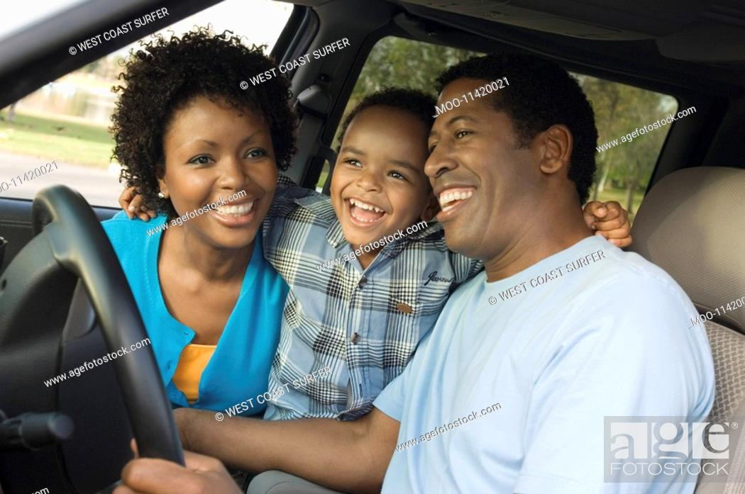 Stock Photo: Family smiling together on driver's seat close-up.