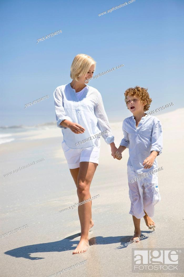 Stock Photo: Woman walking on the beach with her son.
