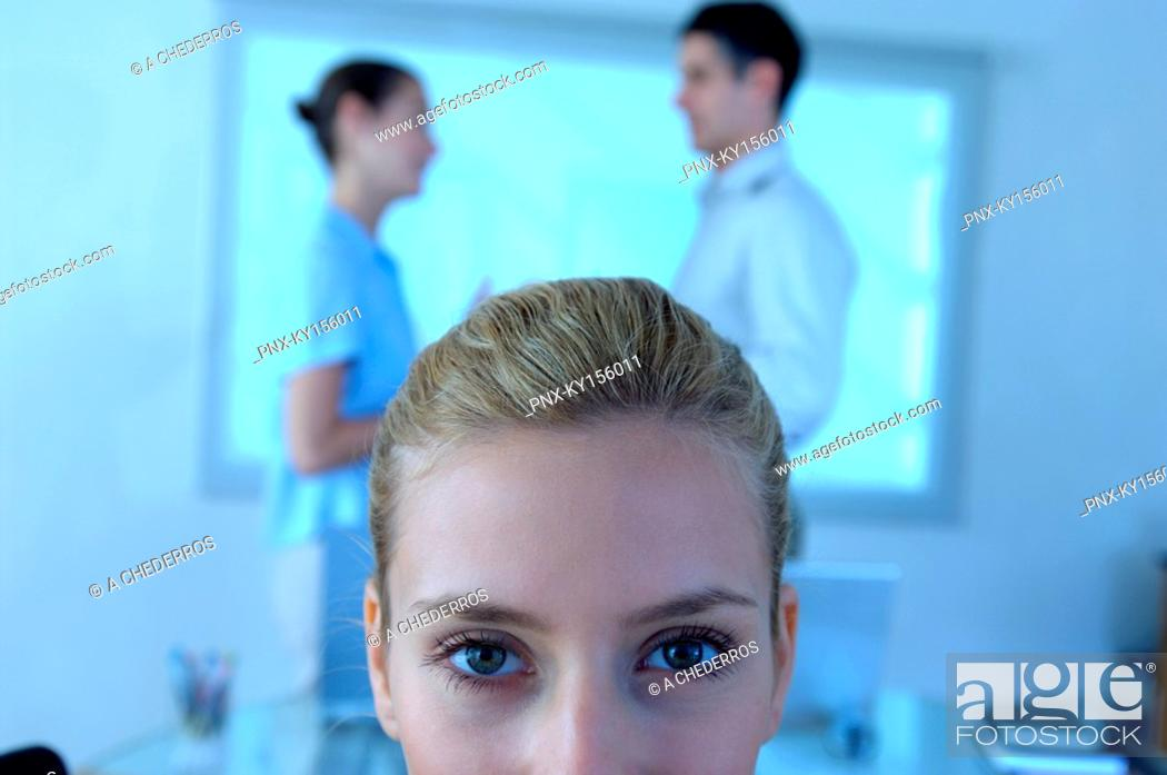 Stock Photo: Businesswoman in office with colleagues standing in background.