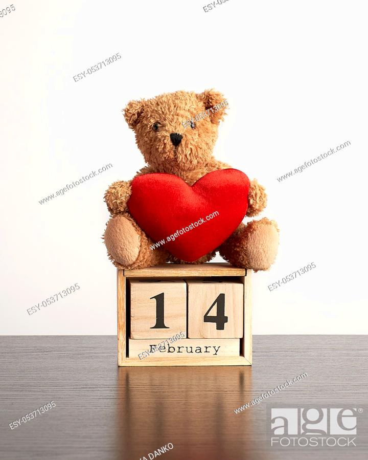 Stock Photo: wooden calendar of cubes with the date of February 14 and a brown teddy bear on a black table, Valentine's Day celebration.