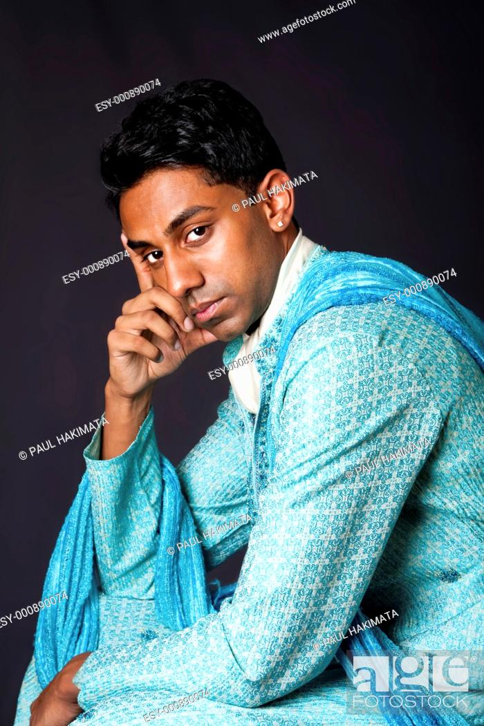 Stock Photo: Beautiful face of an Indian Hindu young man with earring wearing blue Dhoti  Portrait of handsome Desi male sitting and thinking, isolated.