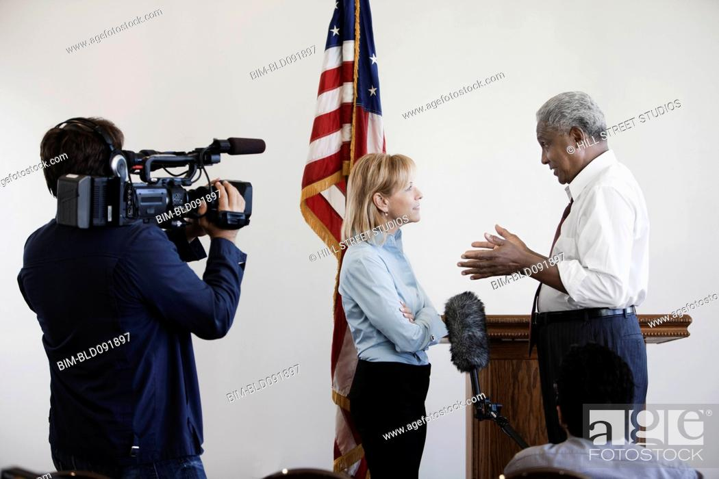 Stock Photo: News reporter interviewing politician on camera.