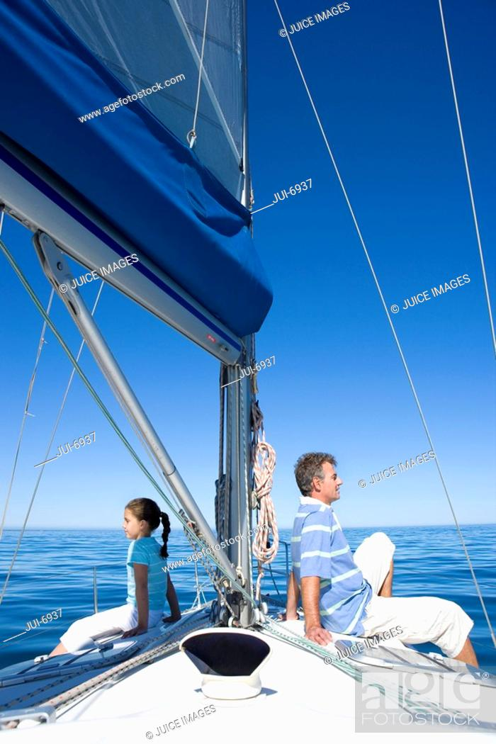 Stock Photo: Father and daughter 8-10 sitting back to back at bow of sailing boat, smiling, profile.