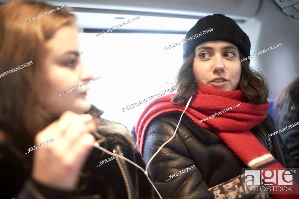 Stock Photo: friends sharing headphones, sharing listening to music or podcast in bus.