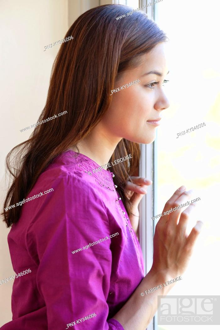 Stock Photo: Profile of a young woman looking out of the window.